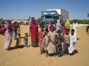 August der Reisewagen: August umringt von einer Familie im Sudan