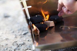Erst anzünden, dann das Blech einhängen und den Kamin mit Kohle füllen.