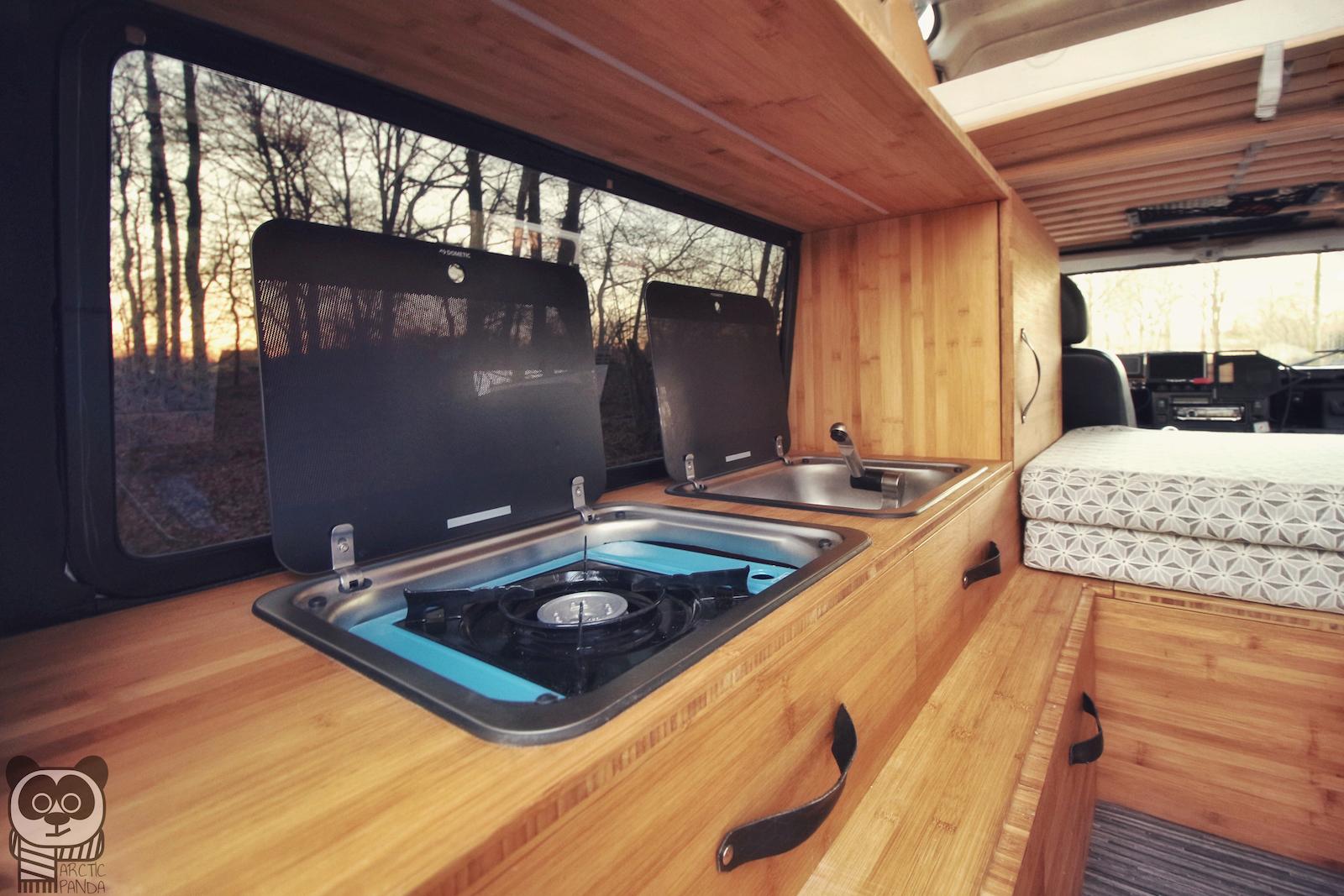 Die Küchenzeile mit Glasabdeckungen: links ein Gaskocher, rechts ein Waschbecken.