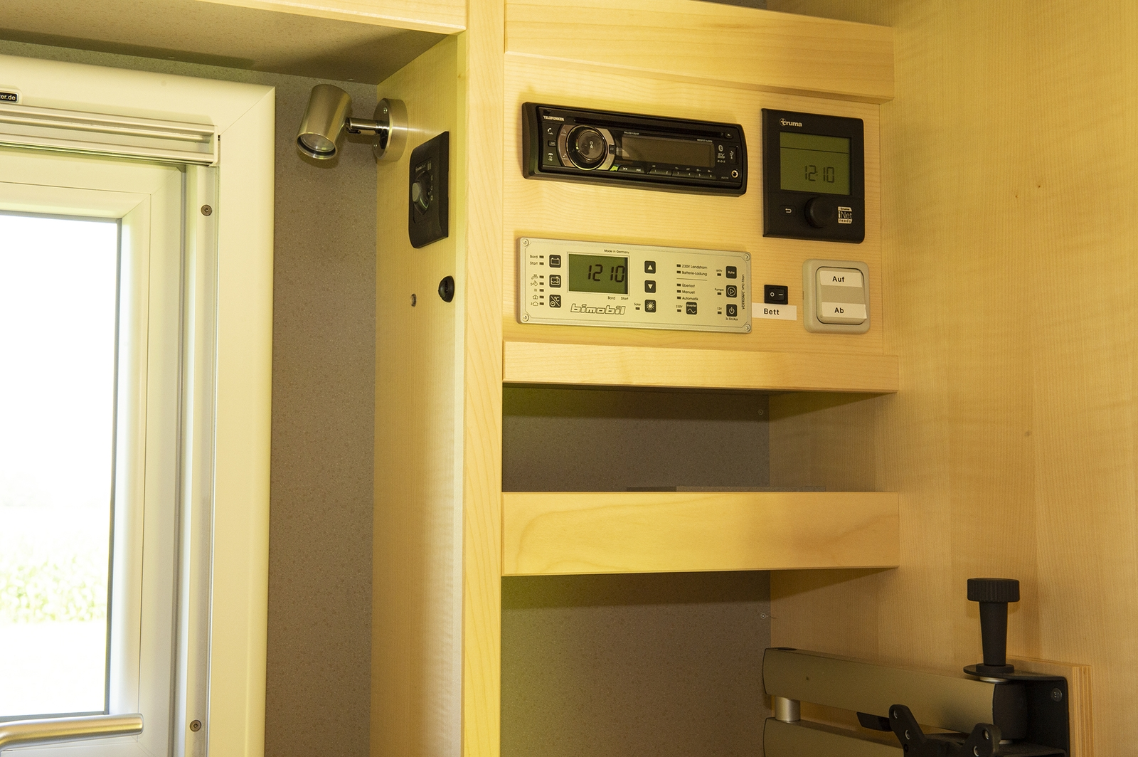 Die Bedienelemente für die Technik und das Radio befinden sich gleich neben der Sitzgruppe. Am Schwenkarm (unten rechts) kann ein Monitor oder ein Fernseher angebracht werden.