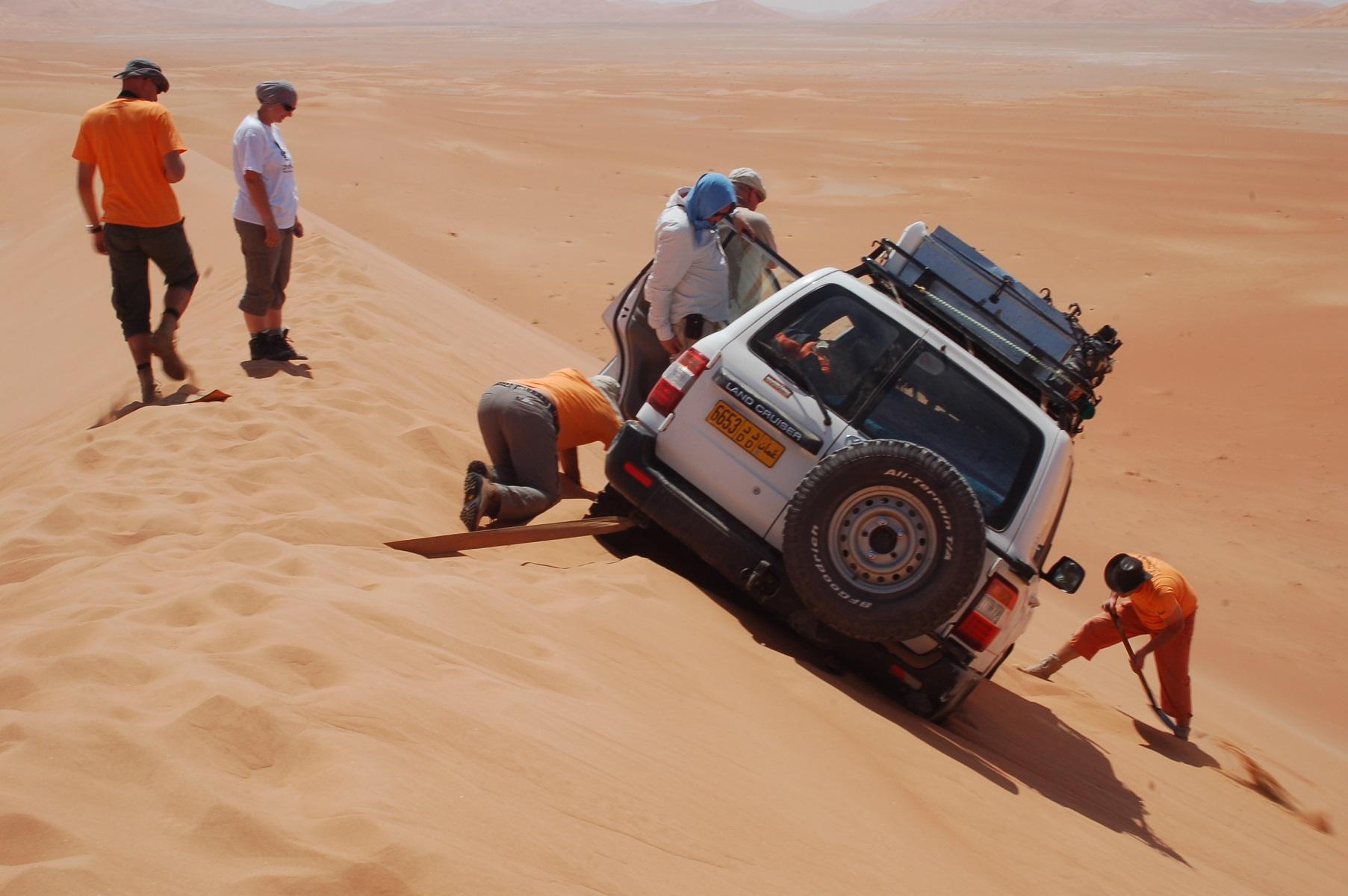 Oman - Der Plan scheint aufzugehen. Aber je weiter sich der Toyota Land Cruiser dreht, um so mehr Sand muss auch unter ihm weg geschaufelt werden. Unter diesen Bedingungen ein Knochenjob.