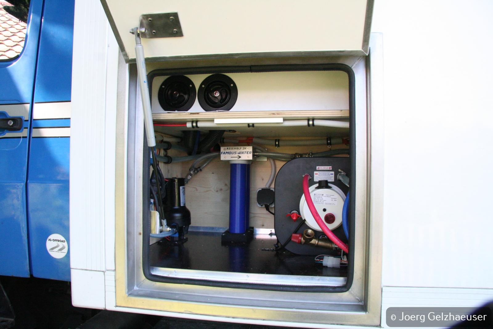 Unimog - Das universelle Motor-(Fernreise)-Gerät - Wasserversorgung mit Druckwasserpumpe, Wasserfilter und Boiler. Befüllstutzen sind innenliegend, getrennte Befüllung und Entnahmeder Wassertanks. Boiler für Warmwasser anfangs noch über 230V, später auch über Motorabwärme.