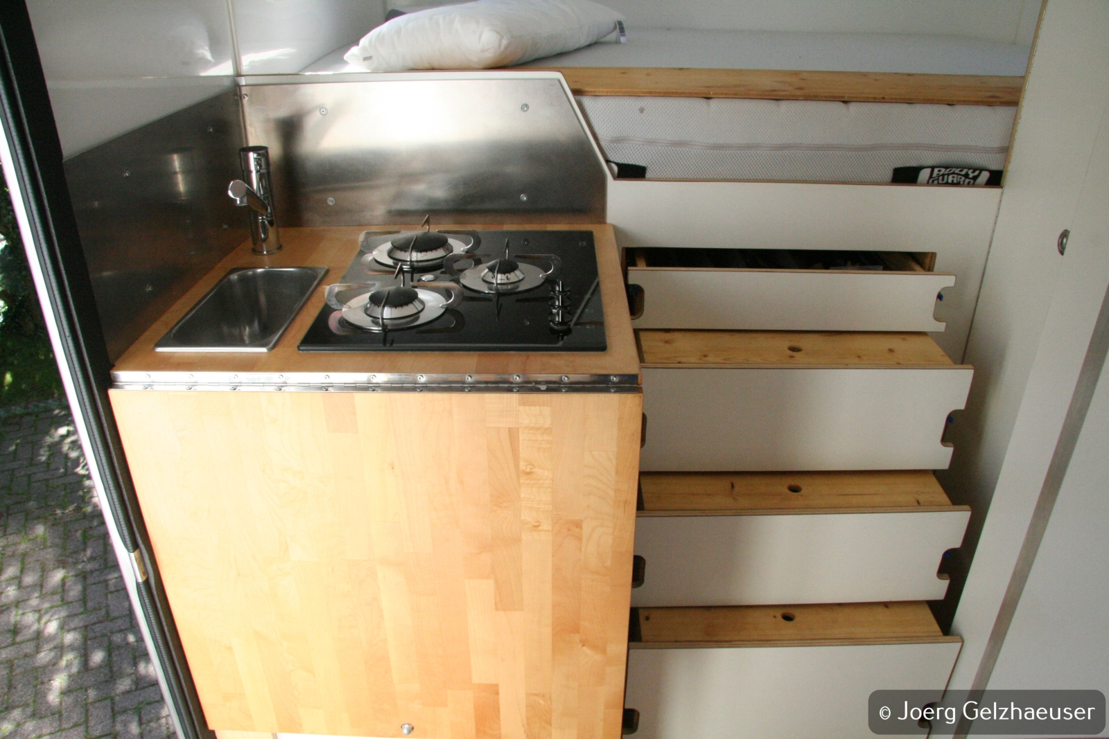 Unimog - Das universelle Motor-(Fernreise)-Gerät - Das große Kochfeld und das kleine Waschbecken samt Arbeitsplattenverlängerung - man(n) muss Prioritäten setzen. Daneben die Schubladen für die Küche auf arretierbaren Schwerlastauszügen. Die beiden unteren dienen zusätzlich als Treppe für das Bett.
