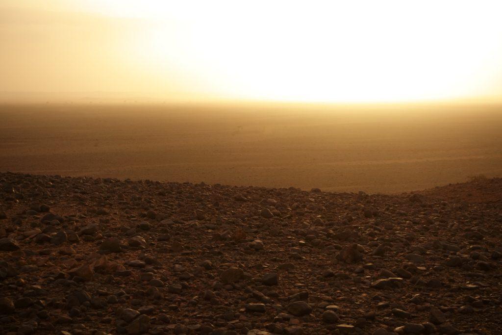 Der Blick über dem Hügel verheißt nichts Gutes, die Dünen liegen da im staubigen Horizont.
