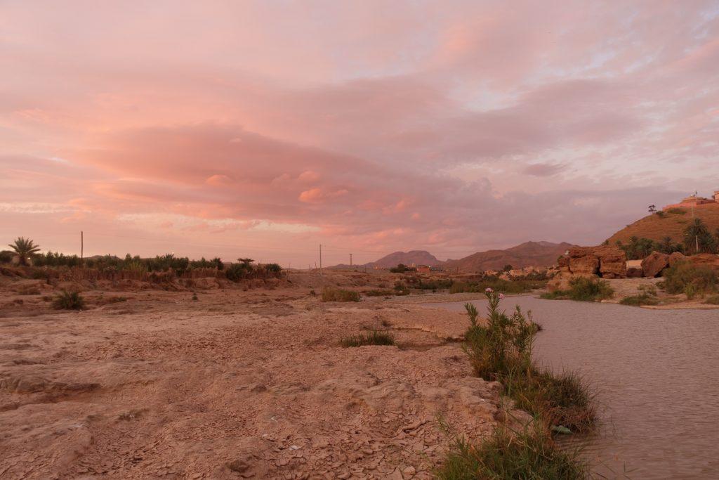 Toyota Land Cruiser in Marokko - Durch den Staub in der Luft verfärbt die untergehende Sonne den Himmel komplett in Rosa.