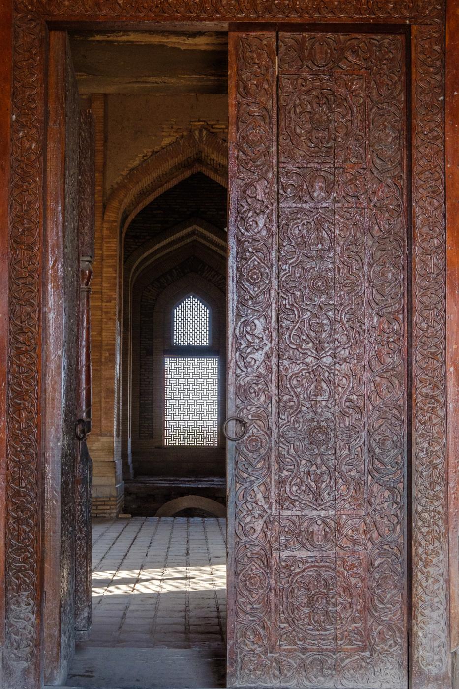Reich verzierte Holztür am Eingang des Mausoleums.