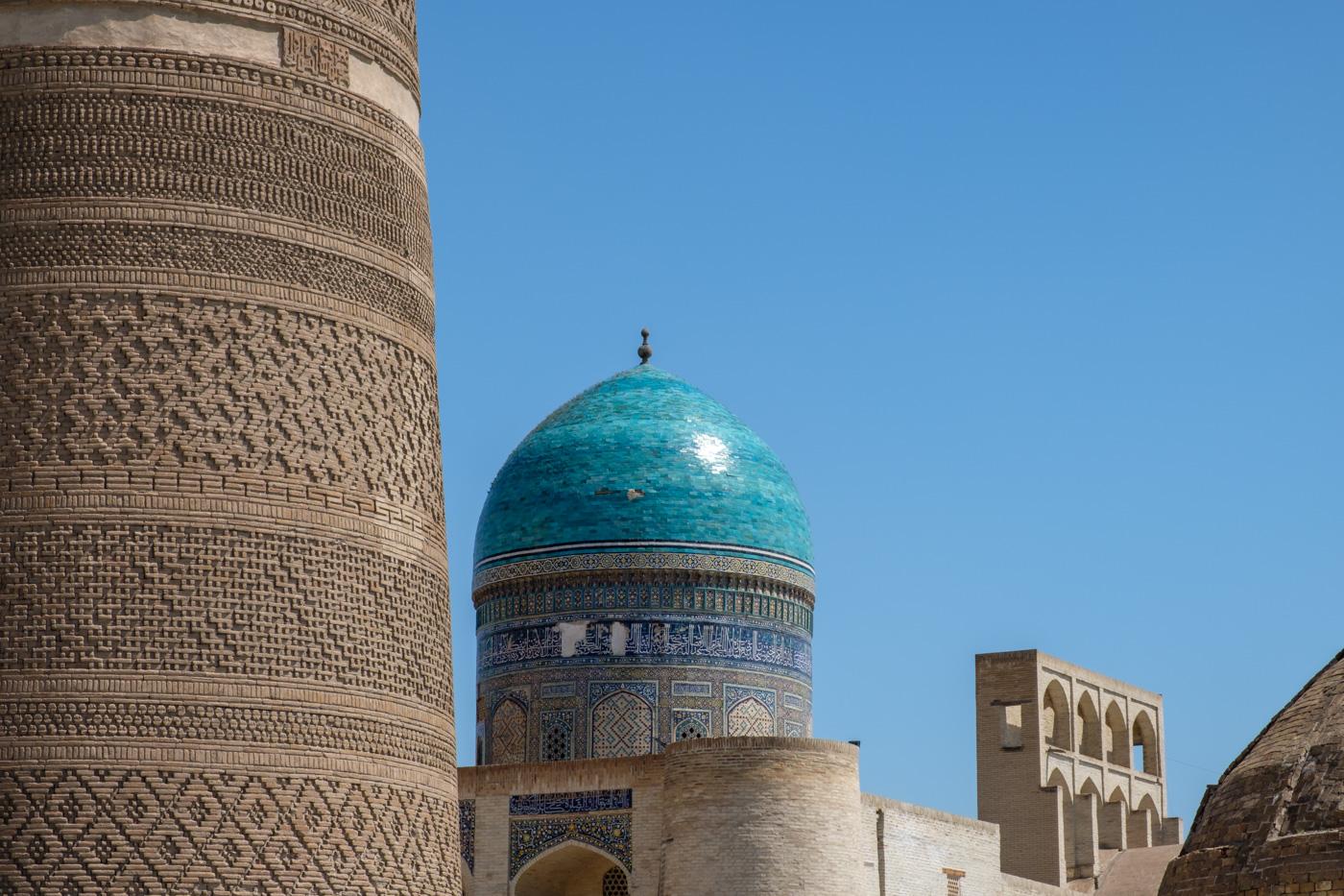 Ziegelmuster des Kalon-Minaretts mit der Kuppel der Mir-Arab Medresse im Hintergrund.