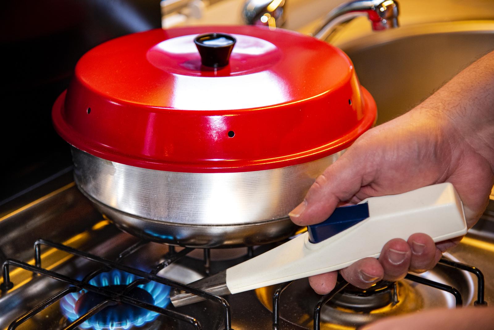 Der Deckel sorgt dafür, dass die Hitze, die durch das Loch in der Mitte aufsteigt, als Oberhitze genutzt wird.