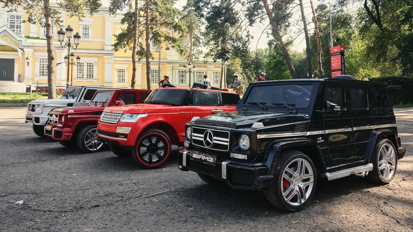 Elektro-Spielzeugautos zum Selberfahren für die Kleinen in Almaty. In den Straßen der Stadt sind auffällig viele der großen Pendants der abgebildeten Fahrzeuge unterwegs.