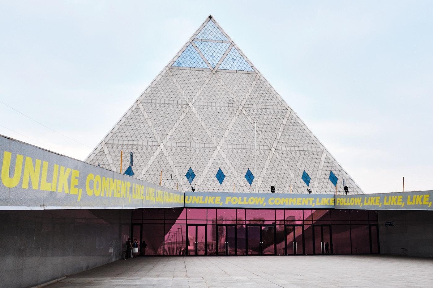 """Pyramide des Friedens und der Eintracht, ebenfalls von Fosters + Partners. Das Bauwerk soll die verschiedenen Religionen in der Welt symbolisieren, ist Tagungsort des """"Congress of Leaders of World and Traditional Religions"""" und beherbergt unter anderem eine Oper mit 1.500 Plätzen sowie mehrere Bildungseinrichtungen."""